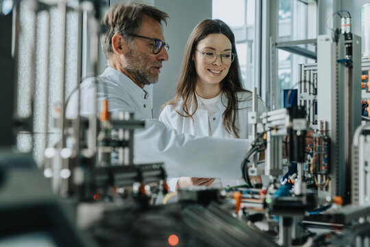 Male and female scientist inventing machinery in laboratory