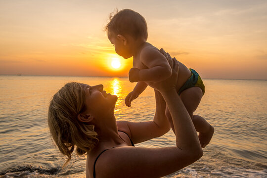 Vietnam, Phu Quoc island, Ong Lang beach, Mother holding baby in beach at sunset