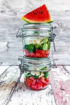 Watermelon slice and jars of watermelon salad with feta cheese, corn salad and mint