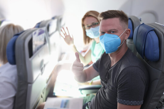 Man with protective mask sit on plane and show his thumbs up. Woman sit next to her husband and wave her hand.