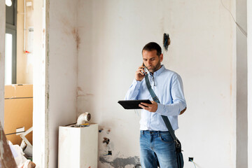 Architect with tablet on the phone in a house under construction