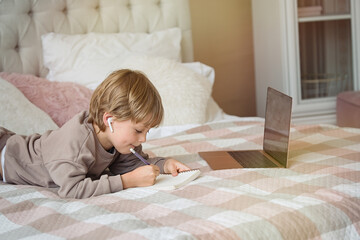 Cute child boy doing homework lying on bed at home. Studying online , distance learning, self education