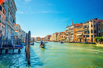 Venice cityscape with Grand Canal waterway, Venetian architecture colorful buildings, gondolier on gondola boat sailing Canal Grande, blue sky in sunny summer day. Veneto Region, Northern Italy.