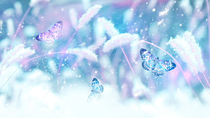 Pink butterflies in flight against the background of wild grass in the snow. Fabulous winter spring image. Magic garden. Winter wonderland.
