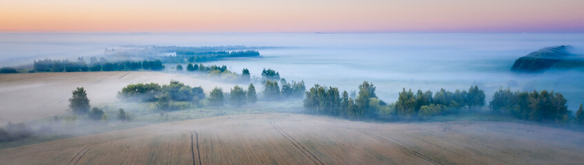Morning fog in the meadows during sunrise in the countryside, aerial view height of the landscape on the horizon, a trees in the fog.