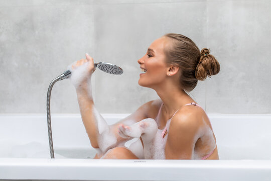 Young woman sing a song holding shower handle in hands in foam in bathroom.