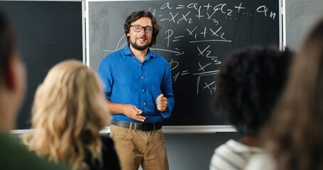 Caucasian man teacher in glasses at school at blackboard talking with pupils or students. Math...