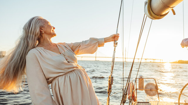 Elderly woman with long hair holding a rope and enjoying sunset on sailboat