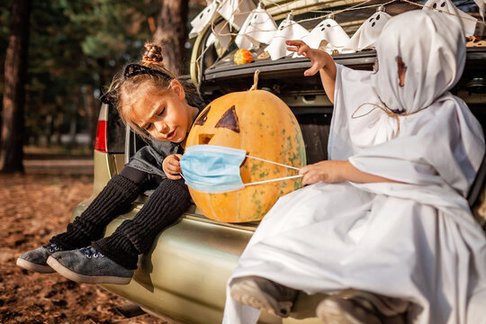 Safe distant Halloween celebration. Kids with decoration at themed party in the trunk of car