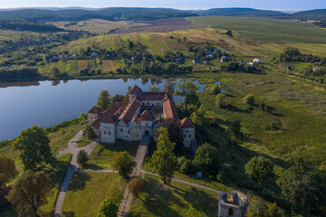 Scenic aerial view on medieval castle on lake shore. Location place: Svirzh, Ukraine. View from flying drone quadcopter .