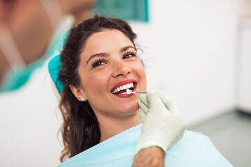 Beautiful woman sitting on dental chair and having dental treatment.