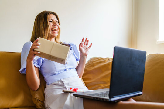 Happy surprised caucasian woman holding birthday presents while laughing and screaming during video call conference at home - Social distance new normal celebrating concept copy space