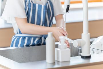 キッチンで手洗いをする女性