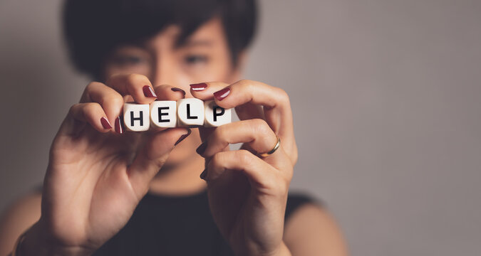 """Portrait of married stylish and sexy woman in black dress stand and holding cubes with word """"HELP"""" in front of her face. Domestic violence awareness concept"""