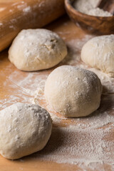 Freshly prepared yeast dough for bread on wooden background.