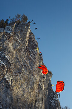 Sequence of BASE jump from a high cliff, bottom view.