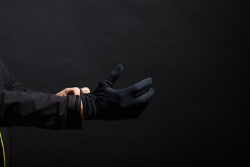 Hand in black gloves of a crime on a black background. Gloves are worn on the hand. The man puts a black glove on his hand.