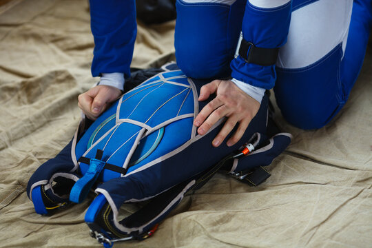 The hands of a male skydiver packed a parachute, face is not visible, close-up.