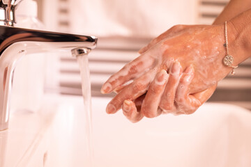 Washing of woman hands with soap under running water, close-up.