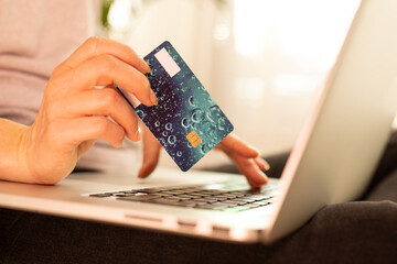 Woman is holding credit card and using laptop computer. Online shopping concept.