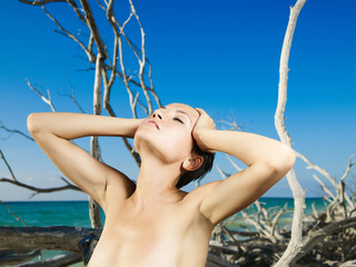 Beautiful nude woman on the beach with driftwood