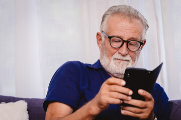 old man looking at the smartphone for reading news update or playing social network apps.