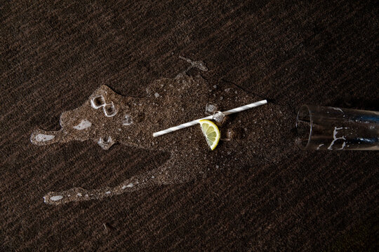 Spilled cocktail, straw and lemon on carpet