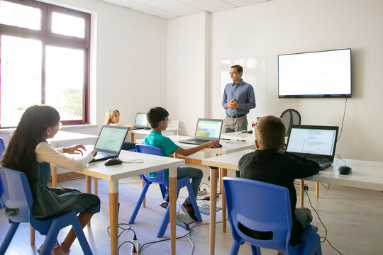 Confident teacher explaining lesson to pupils. Multiethnic children sitting at table in classroom, listening middle-aged man and using laptop computers. Childhood and digital education concept