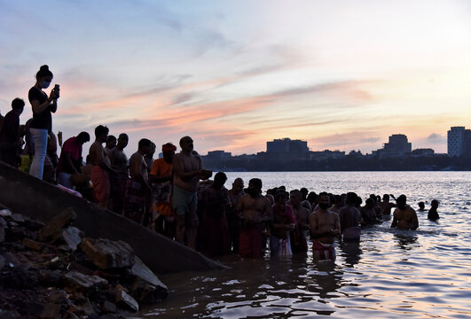 Devotees gather to perform Tarpana on the banks of the Ganges river to honour the souls of their departed ancestors during the auspicious day of Mahalaya in Howrah