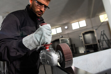 Industrial worker with angle grinder working and polishing stainless steel structure at workshop.