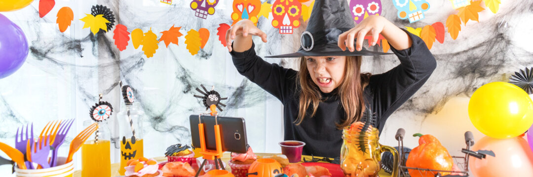 Dressed in spooky halloween costumes girl headwear having video chat on laptop with friends in decorated home. Banner