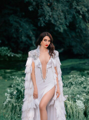 Portrait of a young beautiful attractive woman. White sexy long dress, creative vintage cloak, bird feather cape, shiny rhinestones. Backdrop green trees, river, water grass