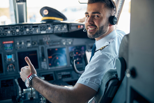 Handsome male posing at the camera in cabin of passenger aircraft