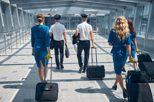 Airline workers carrying travel suitcases at airport terminal