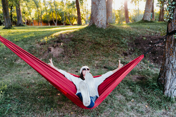 happy woman relaxing in orange hammock. Camping outdoors. autumn season at sunset