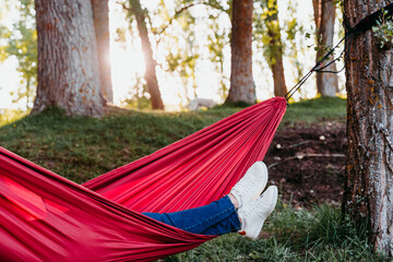 unrecognizable feet of woman relaxing in orange hammock. Camping outdoors. autumn season at sunset