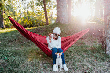 young woman relaxing with her dog in orange hammock. Camping outdoors. autumn season at sunset