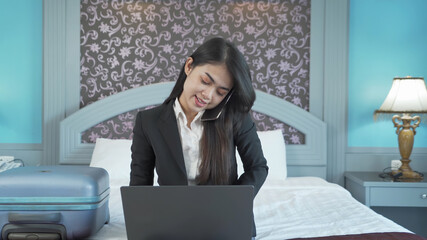 Smiling Asian Thai business woman working from home with computer notebook laptop and talking on mobile smartphone in quarantine in corona virus pandemic concept in bedroom of hotel.