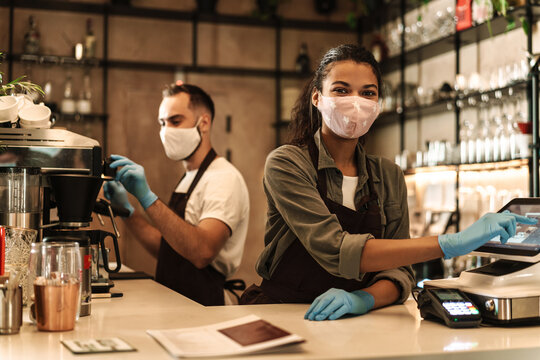 Two baristas wearing medical mask serving coffee