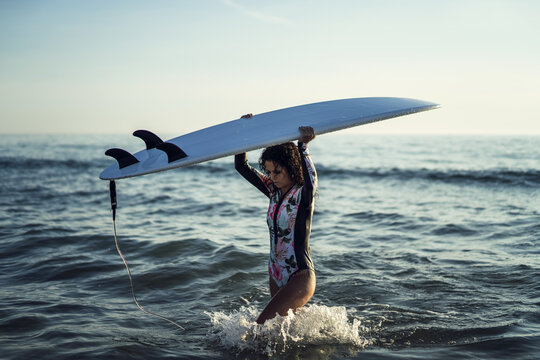 Beautiful young surfer woman  with a surfboard having fun on the beach