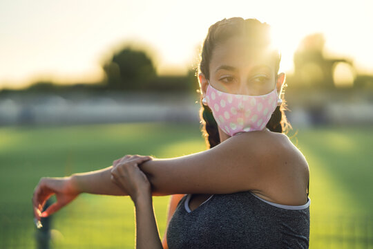 Beautiful female exercising with a protective face mask in the park- COVID-19