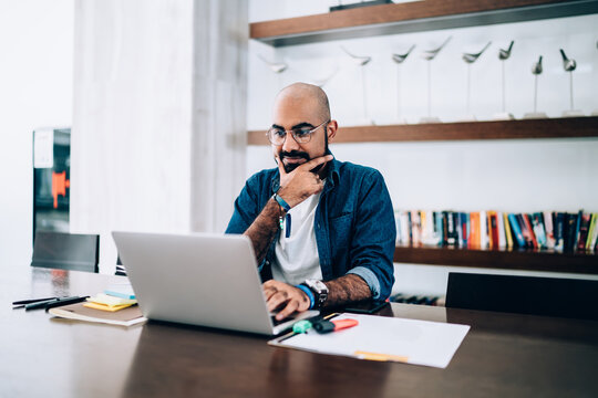 Middle Eastern male entrepreneur in optical eyewear for vision protection sitting at office table desktop with modern laptop computer and watching tutorial webinar,Turkish businessman browsing website