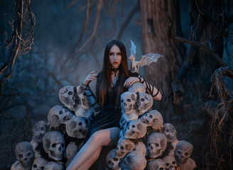 A beautiful sexy vampire woman sits on a throne of the skulls of her victims in a dark mystical forest. Gothic image of the goddess of death with white dragon. dark queen on the hill of skeletons