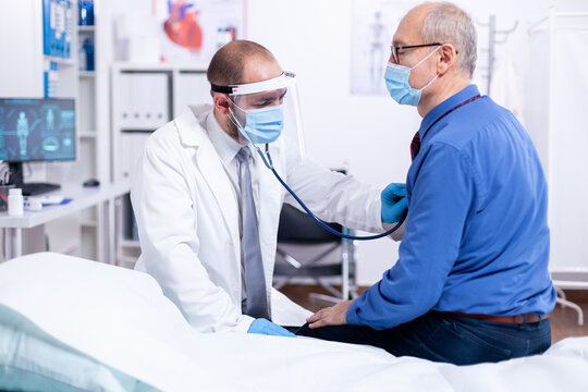 Doctor using stethoscope to listen senior man heart during examination in hospital room and wearing visor as safety precaution against coronavirus. Medical control for infections, disease.