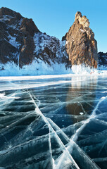 Baikal Lake in winter. Tourists are photographed against the background of the famous Deva Rock (Virgo Rock) or Cape Hoboy - natural landmark of the Olkhon Island. Beautiful landscape