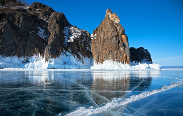 Baikal Lake in February. Beautiful landscape with transparent blue ice near the cliffs of the northern tip of Olkhon Island. View on the famous Deva (Virgo) Rock in the splash ice. Winter ice travel