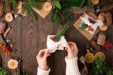 Woman is wrapping gifts in linen fabric on dark rustic wooden background.