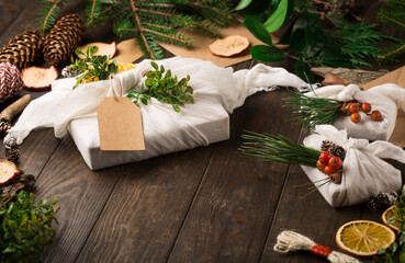 Stylish rustic gifts wrapped in linen fabric with paper envelopes, green branches on wooden table with pine cones, oranges and apples. Flat lay. Simple eco presents plastic free. Zero waste Christmas.