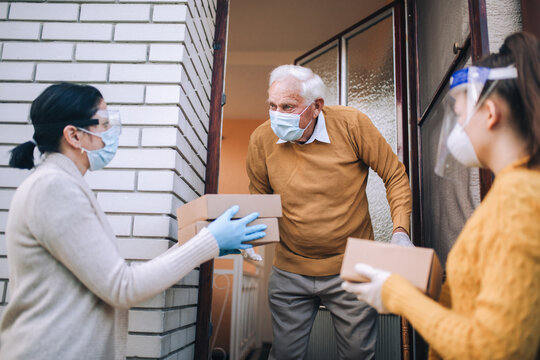 Young female volunteers in mask gives an elderly man boxes with food near his house.