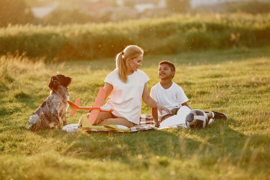 European mother and african son. Family in a summer park. People sitting on the blanket.